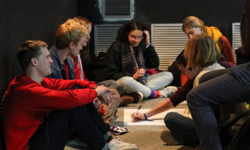 A group of participants sitting on the floor discussing